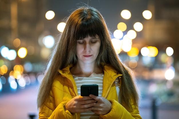 屋外の夜の街の通りで彼女の携帯電話でインターネットを閲覧している若いきれいな女性。