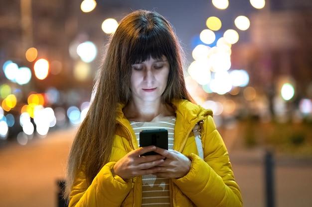 야외에서 밤에 거리 도시에 그녀의 휴대 전화에서 인터넷을 검색하는 젊은 예쁜 여자.