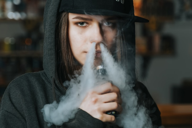 Young pretty woman in cap smoke an electronic cigarette at the vape shop. hip-hop style. closeup.