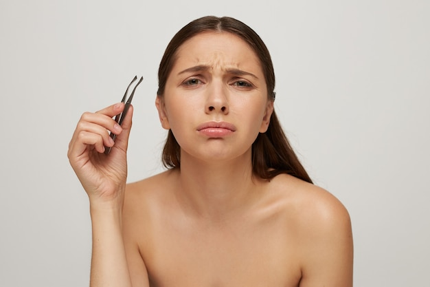 Молодая симпатичная женщина ухаживает за лицом, показывает, как больно вырывать брови