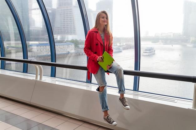 Giovane donna graziosa in abito casual tenendo il tablet portatile in edificio urbano