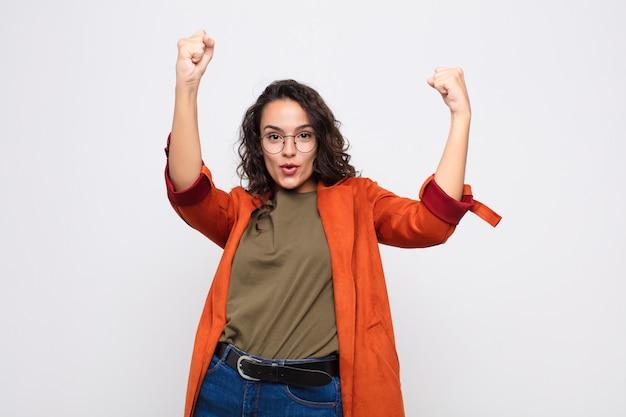 Молодая симпатичная женщина празднует невероятный успех как победительница, выглядит взволнованной и счастливой и говорит: «бери!» против белой стены