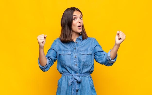 Молодая симпатичная женщина празднует невероятный успех как победительница, выглядит взволнованной и счастливой и говорит: «бери!»