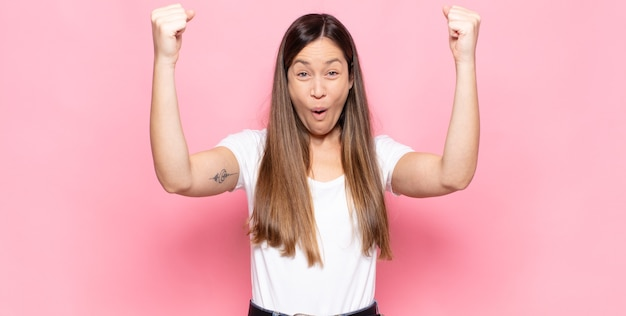 勝者のように信じられないほどの成功を祝う若いきれいな女性は、興奮して幸せそうに見えます。