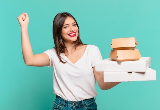 Молодая красивая женщина празднует успешную победу и держит пиццу на вынос