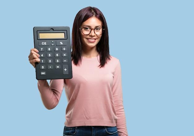 Молодая красивая женщина веселая и улыбчивая, держит калькулятор, делает точные расчеты, данные информации