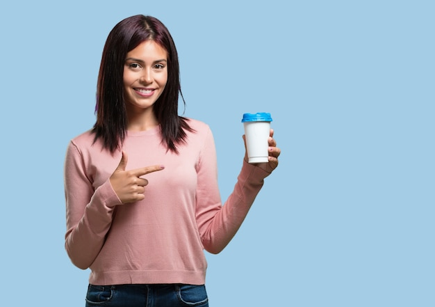 Young pretty woman cheerful and vital, holding a coffee to go, take away beverage