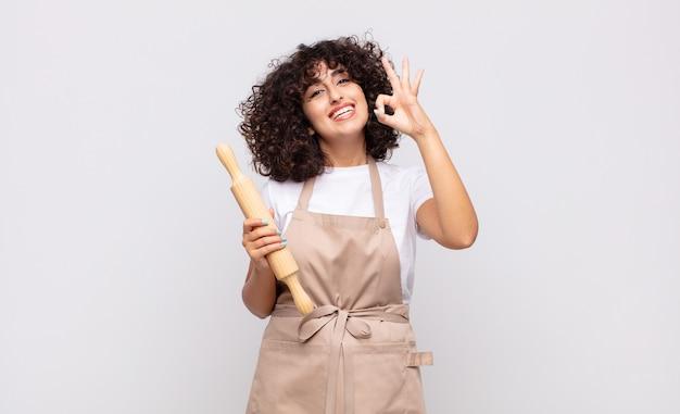 젊은 예쁜 여자 요리사가 행복하고 편안하고 만족스러운 느낌, 괜찮아 제스처로 승인을 보여주는 미소