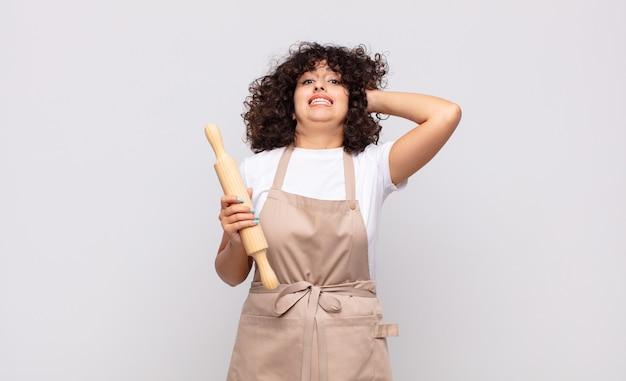 Молодая красивая женщина-повар чувствует стресс, беспокойство, беспокойство или страх, с руками за голову, паникует из-за ошибки