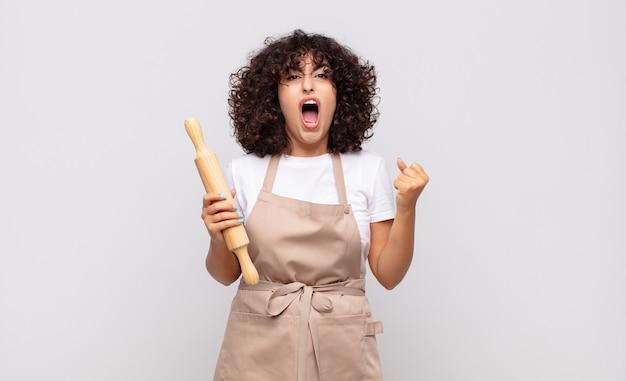 Молодая красивая женщина-повар агрессивно кричит с сердитым выражением лица или со сжатыми кулаками празднует успех