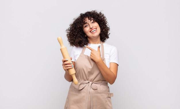 元気に笑って、幸せを感じて、横と上を指して、コピースペースでオブジェクトを示す若いきれいな女性シェフ