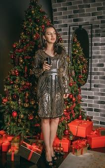 Молодая красивая женщина заделывают под праздничной елкой в помещении с коробками подарков. рождественские фото.