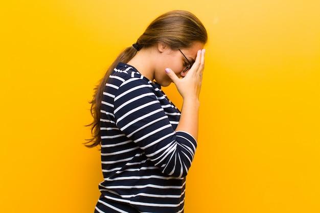 オレンジ色の壁の上の悲しい、失望、泣き、サイドビューの手で目を覆っている若いきれいな女性