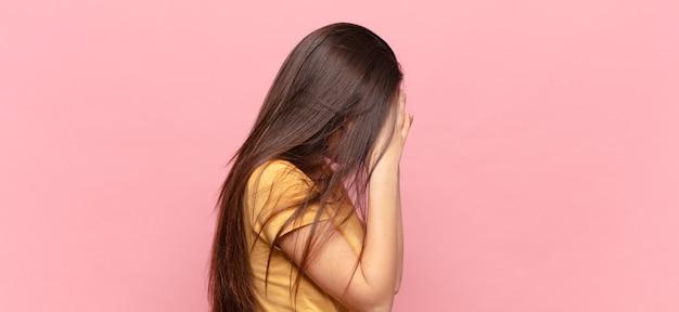 絶望、泣き、側面図の悲しい、欲求不満の表情で手で目を覆っている若いきれいな女性