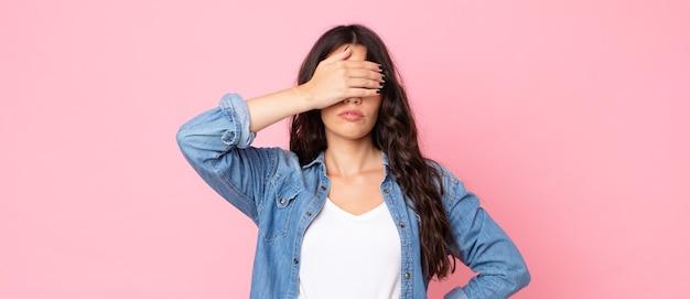 片手で目を覆っている若いきれいな女性は、恐怖や不安を感じ、不思議に思ったり、盲目的に驚きを待っています