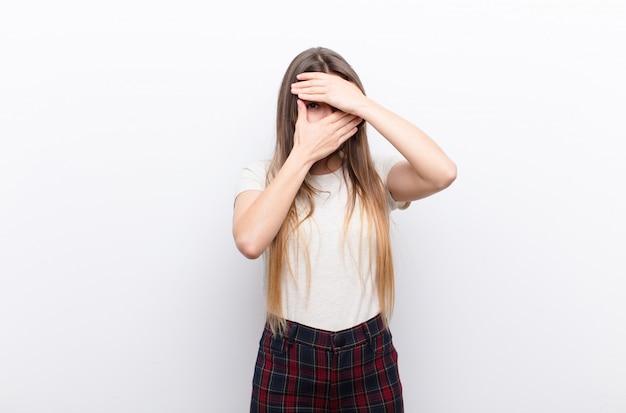 Молодая красивая женщина закрыла лицо обеими руками, говоря нет! отказ от фотографий или запрещение фотографий на белой стене