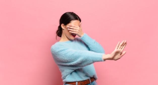 젊은 예쁜 여자가 손으로 얼굴을 덮고 다른 손을 앞에 올려 카메라를 멈추고 사진이나 그림을 거부합니다.