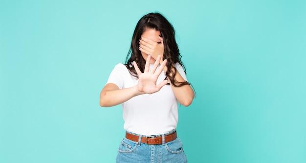 젊고 예쁜 여자는 손으로 얼굴을 가리고 카메라를 멈추기 위해 다른 손을 앞으로 내밀고 사진이나 사진을 거부합니다.