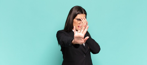 Young pretty woman covering face with hand and putting other hand up front to stop camera, refusing photos or pictures. business concept