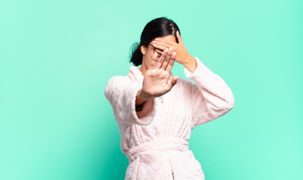 Young pretty woman covering face with hand and putting other hand up front to stop camera, refusing photos or pictures. pajamas concept