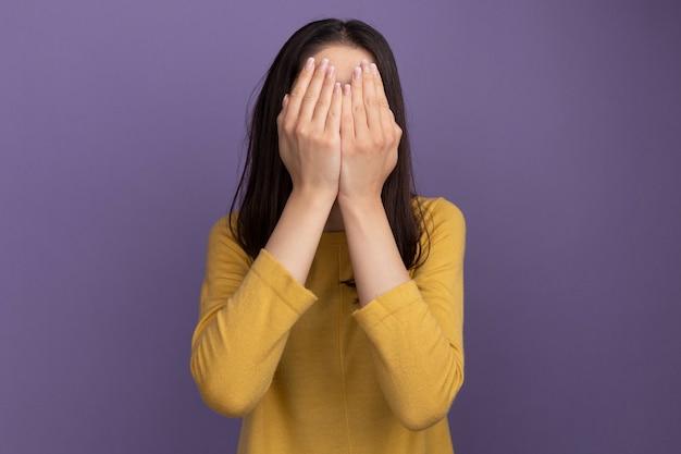 Giovane bella donna che copre il viso con le mani isolate sul muro viola con spazio per le copie