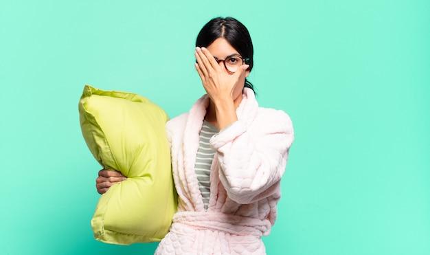 젊은 예쁜 여자 손으로 얼굴을 덮고 놀란 표정으로 손가락 사이를 엿보고 옆을 바라보고 있습니다. 잠옷 컨셉