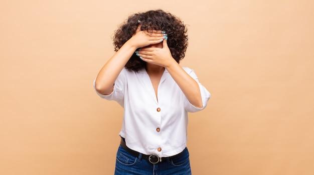 Молодая красивая женщина закрыла лицо вьющимися волосами
