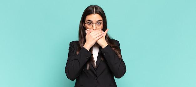 ショックを受けた驚きの表情で口を手で覆ったり、秘密を守ったり、おっと言ったりする若いきれいな女性。ビジネスコンセプト