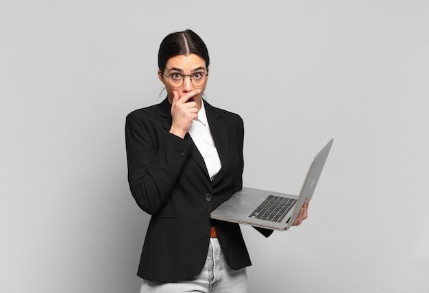 ショックを受けた驚きの表情で口を手で覆ったり、秘密を守ったり、おっと言ったりする若いきれいな女性。ノートパソコンのコンセプト