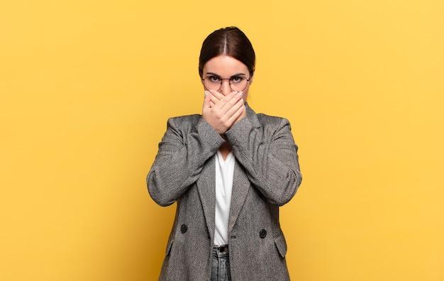 Молодая красивая женщина закрывает рот руками с шокированным, удивленным выражением лица, хранит секрет или говорит: ой