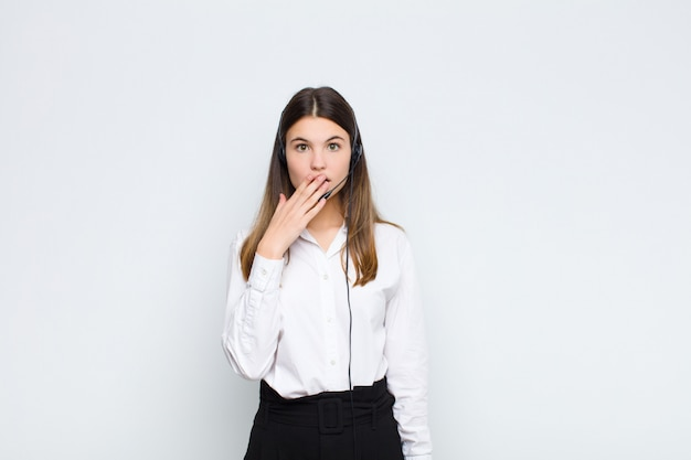 Young pretty woman covering mouth with hands with a shocked, surprised expression, keeping a secret or saying oops with headphones and microphone