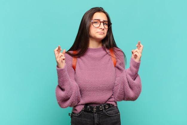 Молодая красивая женщина с тревогой скрещивает пальцы и с тревогой надеется на удачу. студенческая концепция