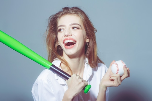 Young pretty woman or cute sexy girl with beautiful long hair and red lips on adorable smiling happy face in fashionable white shirt holds green baseball bat or racket and ball on grey background