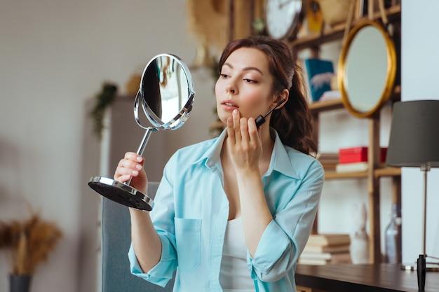 若いきれいな女性は鏡を見ながら自宅で化粧をします