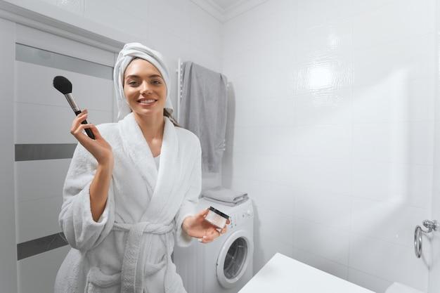 Молодая красивая женщина делает макияж лица дома