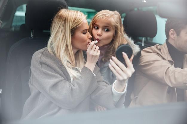 鏡を見て化粧をしている若いきれいな女性