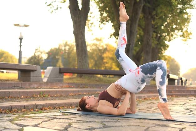 公園でヨガの練習をしている若いきれいな女性。