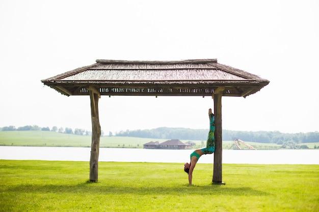 Молодая красивая женщина занимается йогой в утреннем парке возле озера