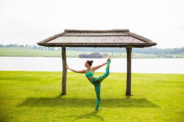 Giovane donna graziosa che fa yoga nel parco di mattina vicino al lago