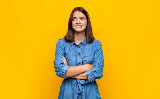 Молодая красивая женщина сомневается или думает, кусает губу и чувствует себя неуверенно и нервно, пытаясь скопировать пространство сбоку