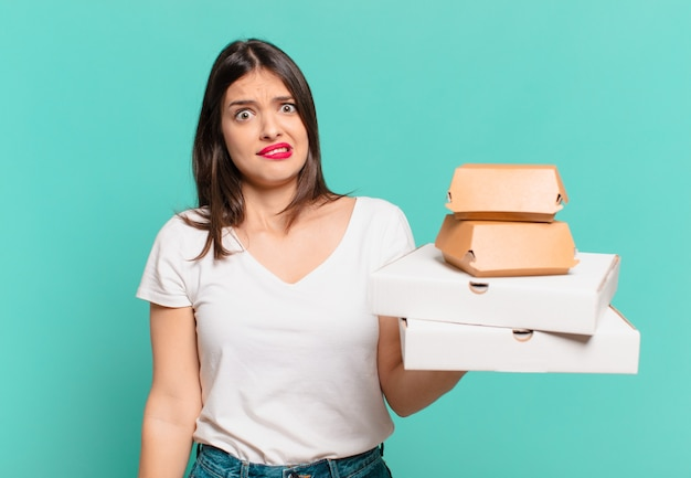 Молодая красивая женщина, сомневающаяся или неуверенное выражение и держащая пиццу на вынос