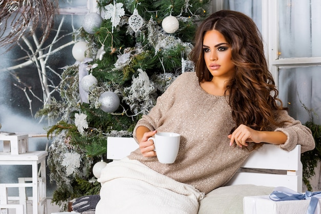 Young pretty woman  dreaming and drinking coffee or tea, enjoying   christmas morning, close up portrait of  beautiful  lady in warm cozy clothes sitting on  light  decorated  terrace