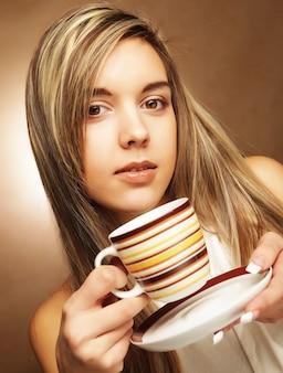 Молодая красивая женщина пьет кофе на бежевом фоне