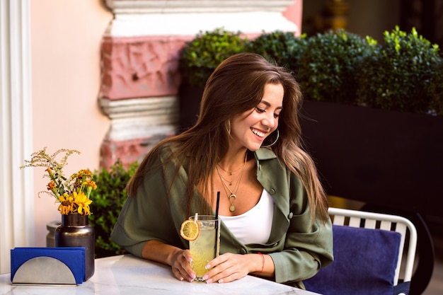 シティテラス、カジュアルな流行の服、週末、旅行の気分でおいしい甘いカクテルを飲む若いきれいな女性。