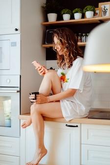 若いきれいな女性は、自宅のキッチンに座って、スマートフォンを使用して朝の楽しみをコーヒーを飲みます