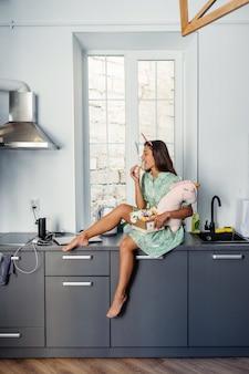 Молодая красивая женщина ест торт в современной кухне. домашняя одежда.