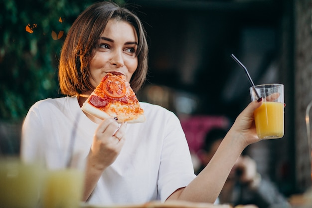 Young pretty woman eating pizza at a bar