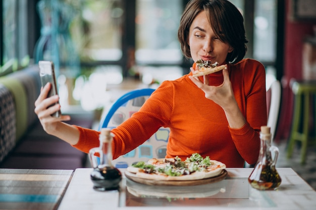 Young pretty woman eating pizza at pizza bar