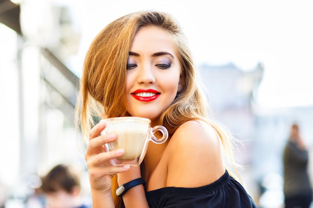 Young pretty woman enjoying, drinking cup of cappuccino, latte, coffee in morning street cafe.