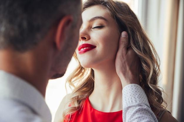 Young pretty woman enjoying her man touching